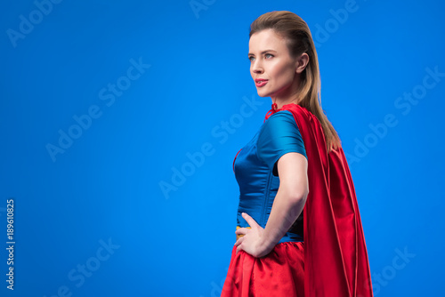 Photo  side view of beautiful woman in superhero costume standing akimbo isolated on bl
