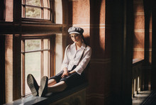 Young Girl Retro Hooligan In A Cap  Sitting On The Window. A Woman Is Dressed Like A Man, A Vintage Style. Times Of The Great Depression