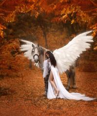 Piękna, młoda elfka, spacerująca z jednorożcem. Ma na sobie niesamowitą lekką, białą sukienkę. Dziewczyna leży na koniu. Fotografia artystyczna