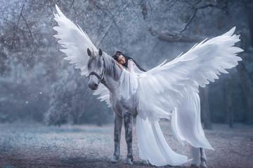 Piękna, młoda elfka, spacerująca z jednorożcem. Ma na sobie niesamowitą lekką, białą sukienkę. Dziewczyna leży na koniu. Śpiąca Królewna. Fotografia artystyczna