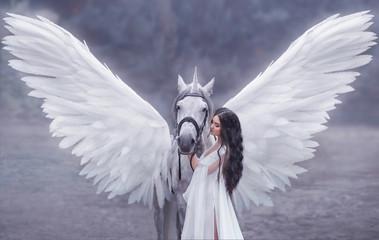 Piękna, młoda elfka, spacerująca z jednorożcem. Ma na sobie niesamowitą lekką, białą sukienkę. Hotografia artystyczna