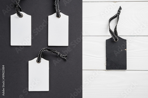 empty white tags in a row on white and black wooden background top