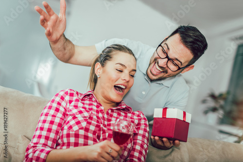 Obraz na plátně Smiling young man surprising cheerful woman with a gift box at home