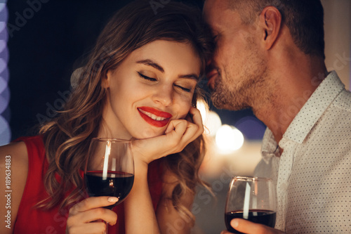Obraz Young handsome man whisper to his woman while have romantic dinner - fototapety do salonu