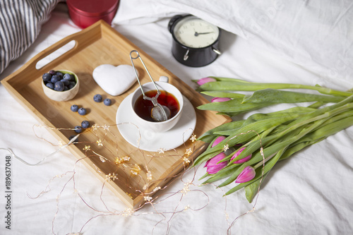 Stickers pour porte Pique-nique tray with tea and gingerbread in the shape of heart and a bouquet of tulips on the bed