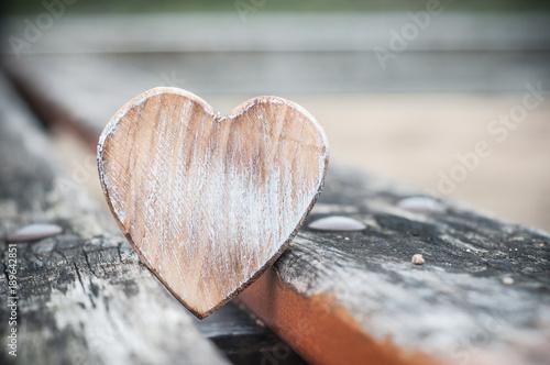 coeur en bois sur un banc dans un jardin public Poster
