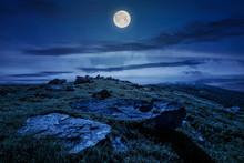 Rocky Formation On Grassy Hillside. Beautiful Scenery Of Runa Mountain In Summertime At Night In Full Moon Light. Location Carpathian Mountains, Ukraine
