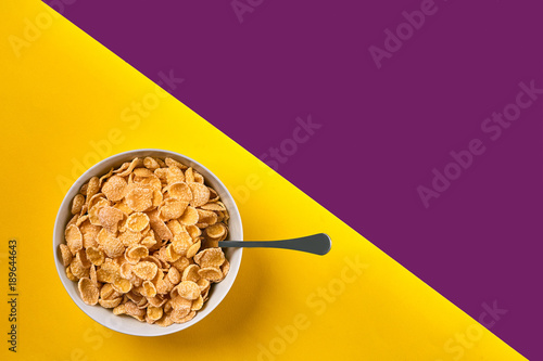 Cuadros en Lienzo Bowl with corn flakes and spoon on purple and yellow background, top view