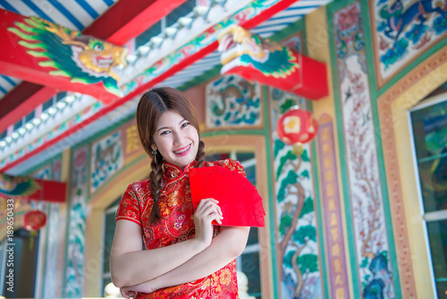 Tuinposter Imagination Portrait of beautiful asian woman in Cheongsam dress with Red envelope in hand,Thailand people,Happy Chinese new year concept