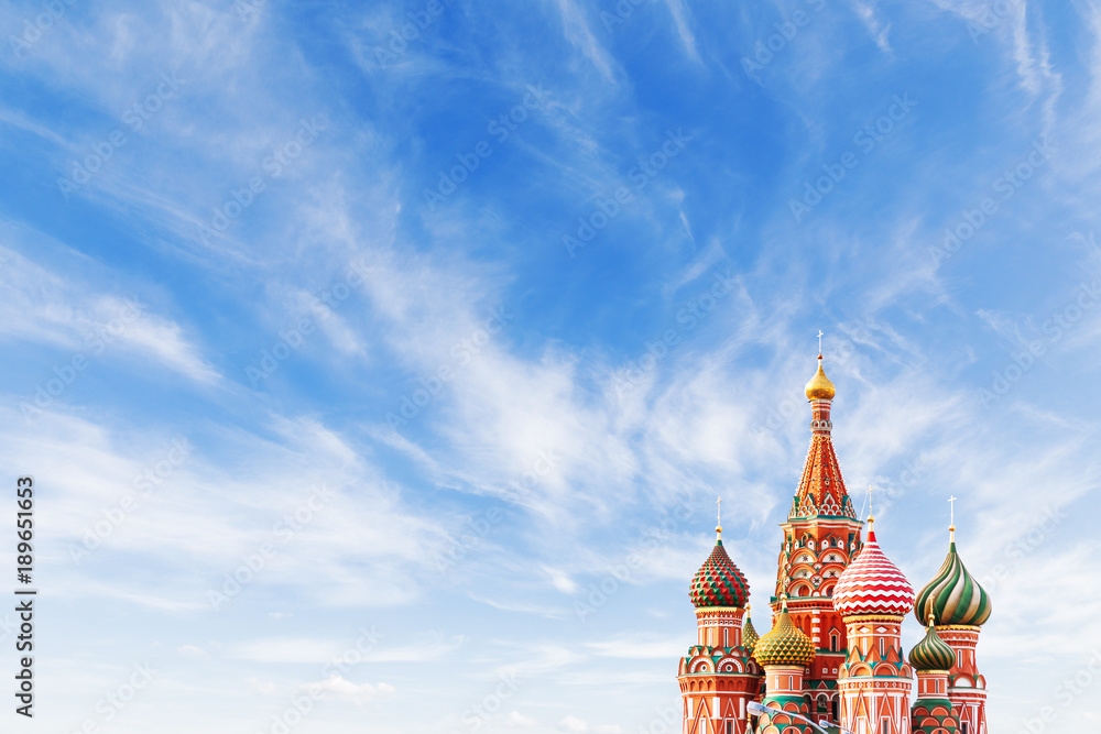 Fototapety, obrazy: Domes of Saint Basil Cathedral on blue sky background. Famous landmark of Moscow, Russia. Bright sunny day with clouds. Cloudscape on blue sky. Place for text.