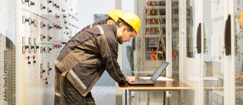 Fotografiet  Two maintenance engineers inspect relay protection system with laptop comp