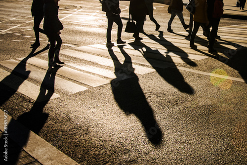 Blurry people and their shadows on crossing Fototapet