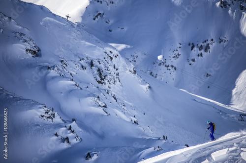 Freeride skier skiing down across the slope #189666623