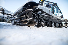 Close Up View Of Special Snow Vehicle With The Caterpillar On The Snow In Winter.