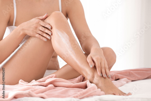 Fototapeta Woman applying body cream on her leg in bedroom, closeup