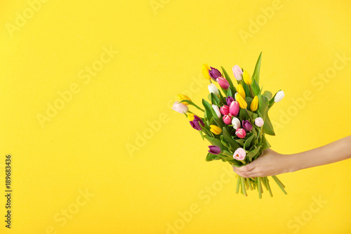 Fotografía  Woman holding bouquet of tulips on color background