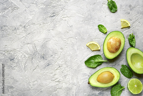 Avocado halves with lime slices and baby spinach leaves .Top view with copy space. © lilechka75