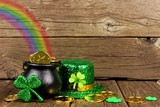 Fototapeta Tęcza - St Patricks Day Pot of Gold with rainbow, shamrocks and hat against rustic wood
