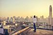 Western businessman looking at Bangkok City at sunset