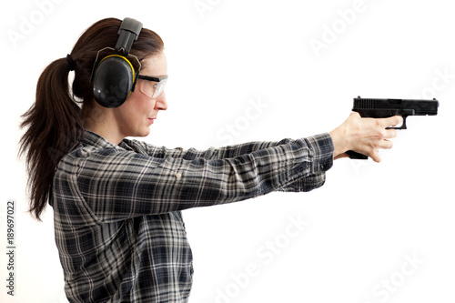 Second amendment, self defence and use of firearms at shooting range concept with a woman aiming a gun and ready to shoot while wearing protective gear isolated on white with a clipping path included
