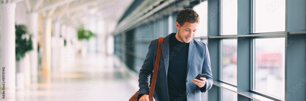 Fototapety, obrazy: Man holding phone - young businessman using smartphone in airport. Casual urban professional business man texting cellphone happy inside office banner panorama with copy space on background.