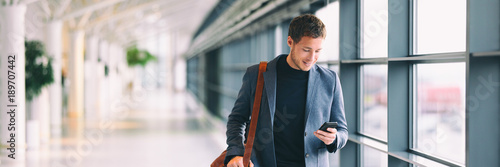 Fotografia  Man holding phone - young businessman using smartphone in airport