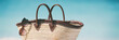 Beach vacation summer winter getaway banner panoramic background concept- Beach bag and sunglasses for Caribbean travel holiday. Copy space on blue ocean. Fashion accessories.