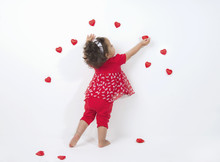Mixed Race, Little, Girl Decorates White Wall With Red Hearts For Valentine's Day