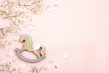 Pink Background With Mini Rocking Horse Toy And Gypsophila Flowers. Copy Space.