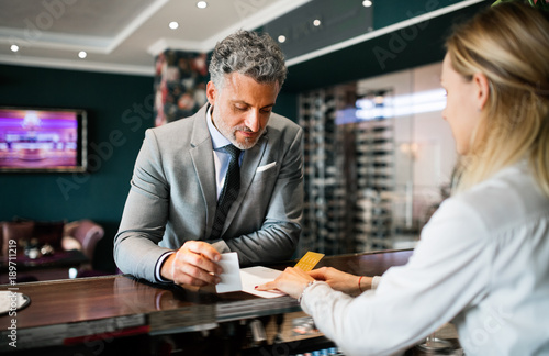 Mature businessman at hotel reception.
