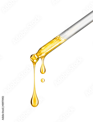 Fototapeta Cosmetic pipette with drops of cosmetic oil close-up on a white background obraz