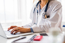 Female Doctor With Laptop Work...