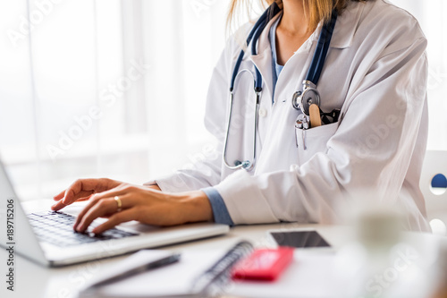 Fotografia  Female doctor with laptop working at the office desk.