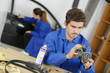 student with auto part studying automotive trade