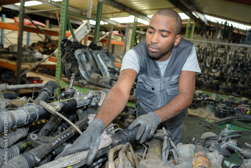 Mechanic at stack of used car parts Wallpaper Mural