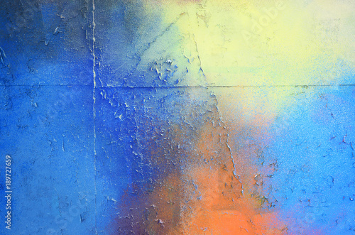 plakat A large fragment of the graffiti pattern applied to the wall with aerosol paint. The gradient between several colors is carried out by spraying the paint. Abstract background image