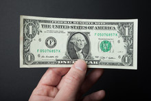 One Dollar Close-up In Hand On A Black Background.