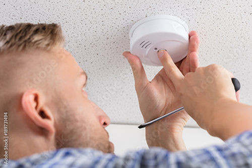 Valokuva  Person's Hand Installing Smoke Detector On Ceiling