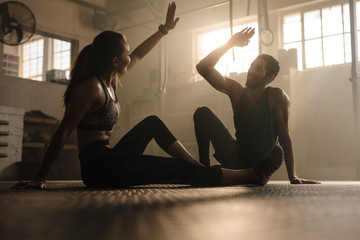 Fit couple high five after workout in health club