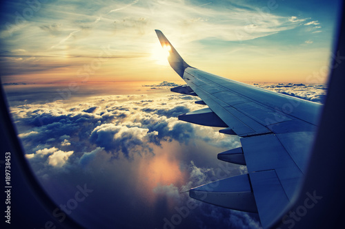 Poster Airplane flying and traveling, view from airplane window on the wing on sunset time