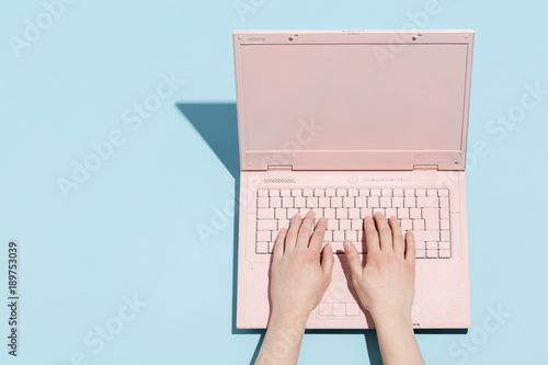 Woman's hands typing on a pastel pink keyboard