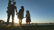 Leinwandbild Motiv Portrait of happy family at sunset - father, mother, daughter and little son - silhouette