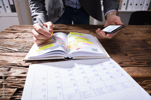 Businessperson Writing Schedule In Diary Canvas Print