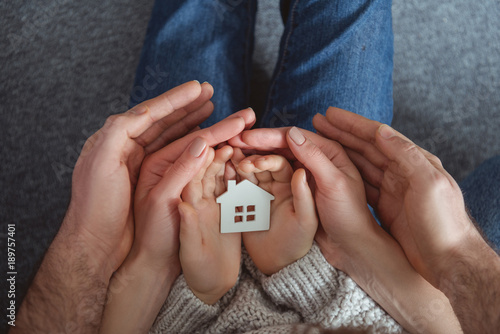 Cropped Shot Of Family Holding Small House Model In Hands Buy