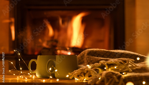 Steam from cups with hot cocoa on the fireplace background.   Decoration garlands of lights .