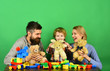 Parenthood and game concept. Mom, dad and kid in playroom.