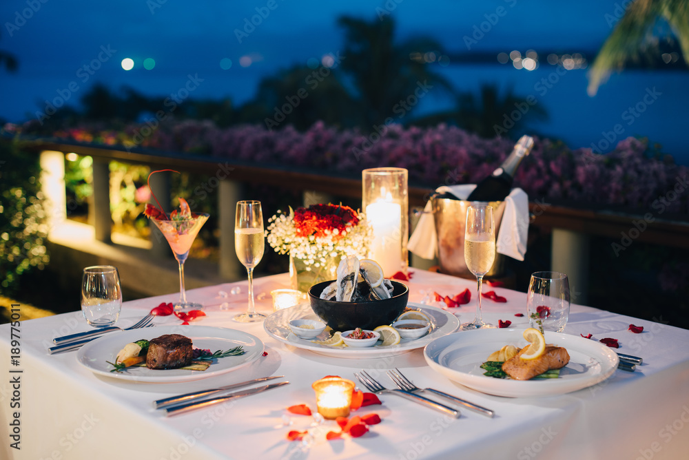 Fototapeta Romantic candlelight dinner table setup for Valentine's day with Champaign & wine glasses and special dishes