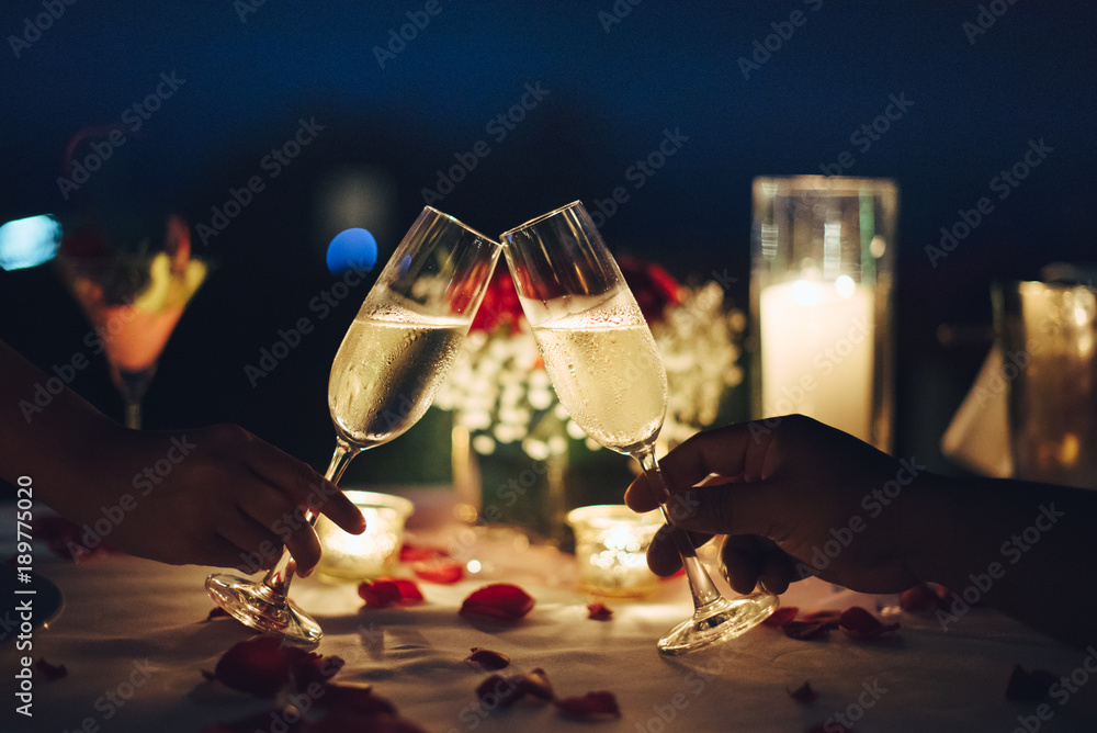 Fototapeta Romantic candlelight dinner table setup. Man & Woman hold glass of Champaign.