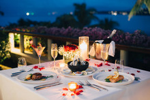 Romantic Candlelight Dinner Luxury Table Setup For Couple With Beautiful Light As Background. Glasses Of Champagne And Beautiful Food Presentation On Table.. Concept For Valentine's Day  And Date.