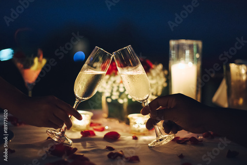 Fototapeta Romantic candlelight dinner table setup for couple with beautiful light as background. Man & Woman hold glass of Champaign. Concept for valentine's day and date. obraz